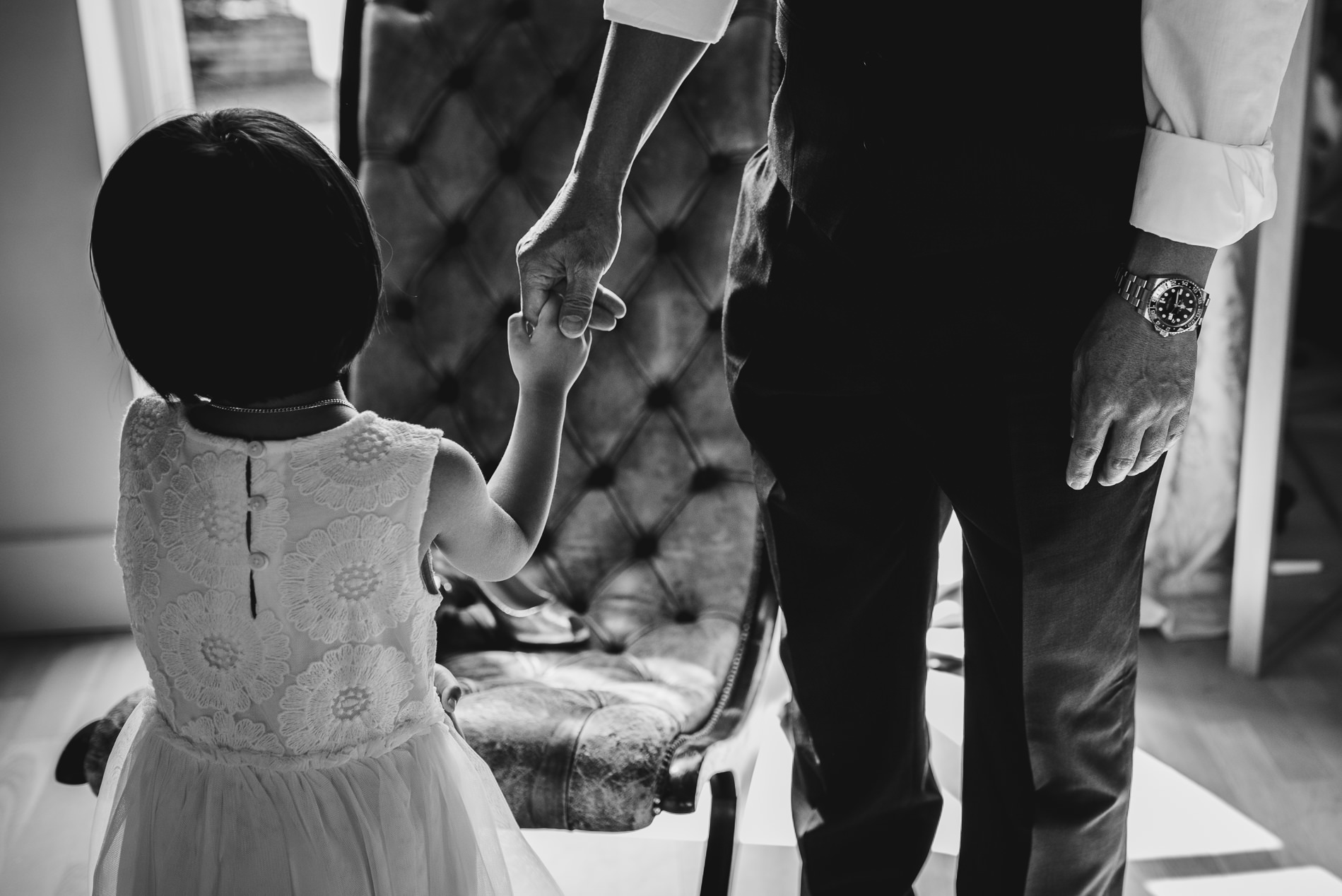 flower girl holiding dad's hand at White Dove Barn