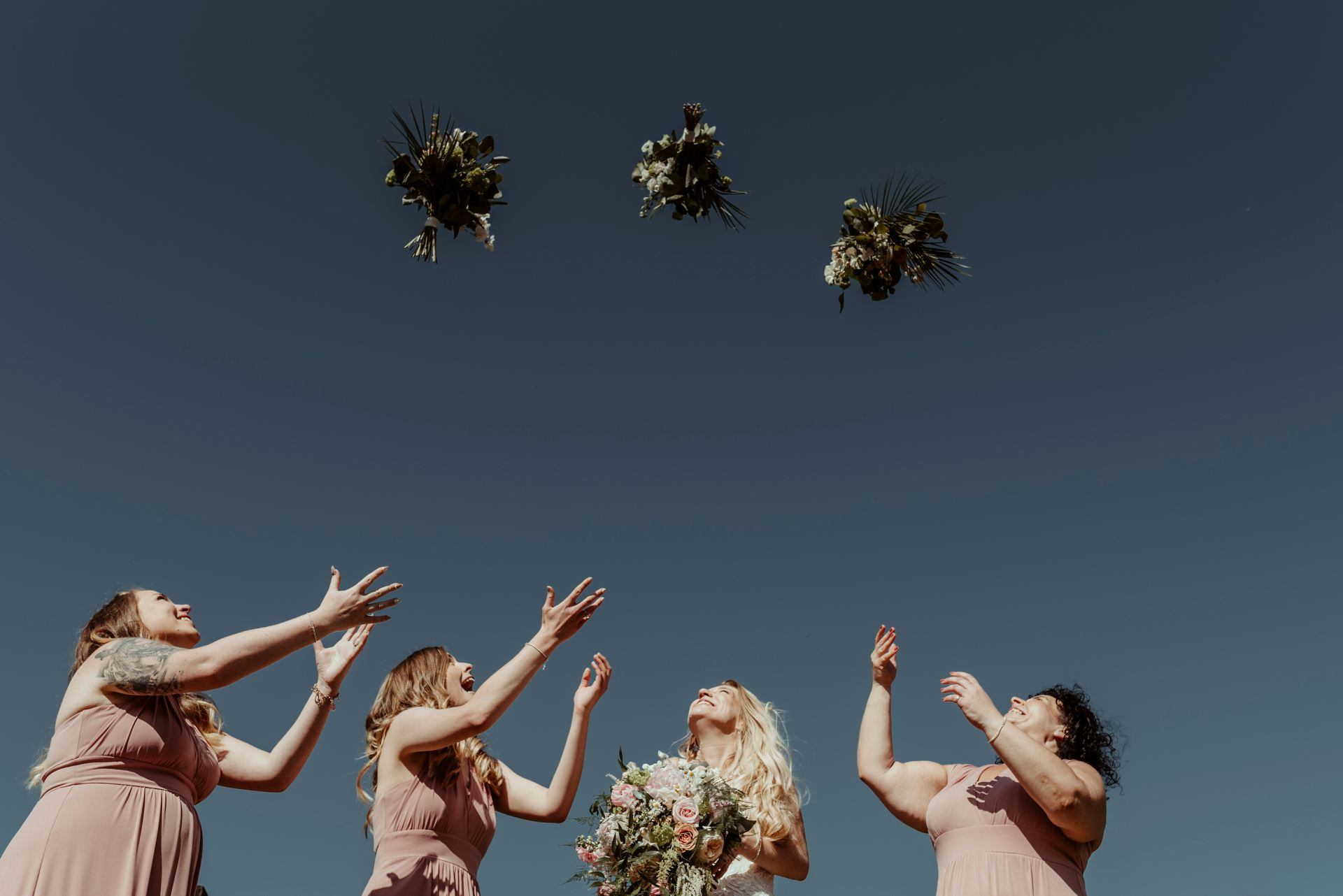bridesmaids throwing bouquet at Essex Wedding