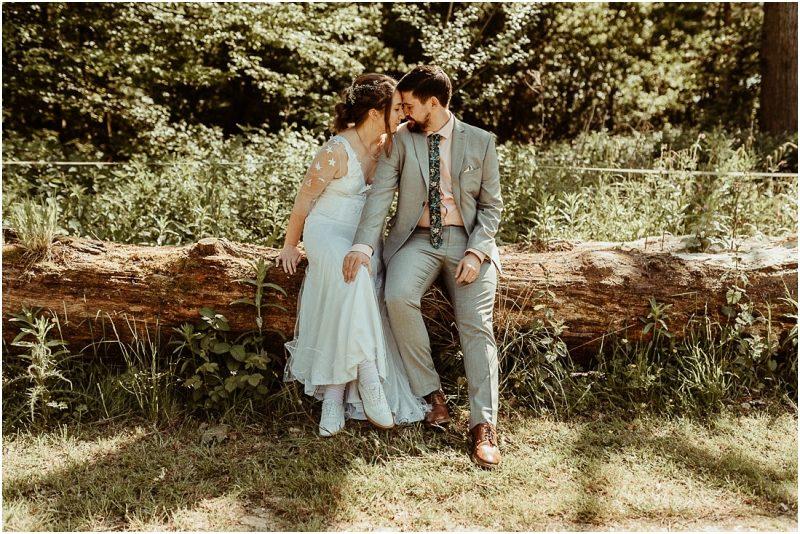 Captain's Wood Barn Essex DIY Dress Couple sitting on log