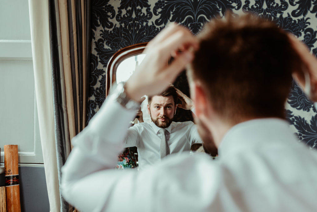 Groom styling hair at Hengrave Hall
