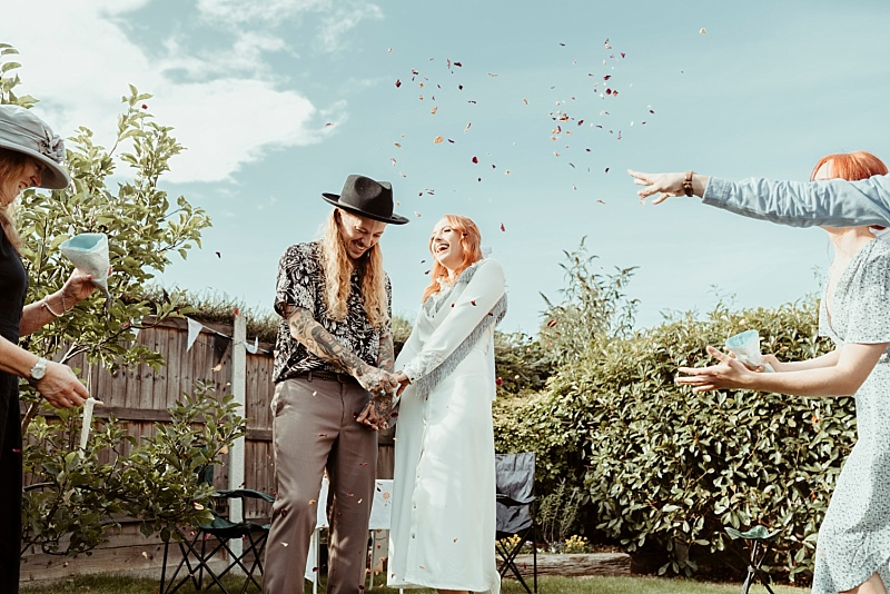 Wedding couple with confetti in small back garden